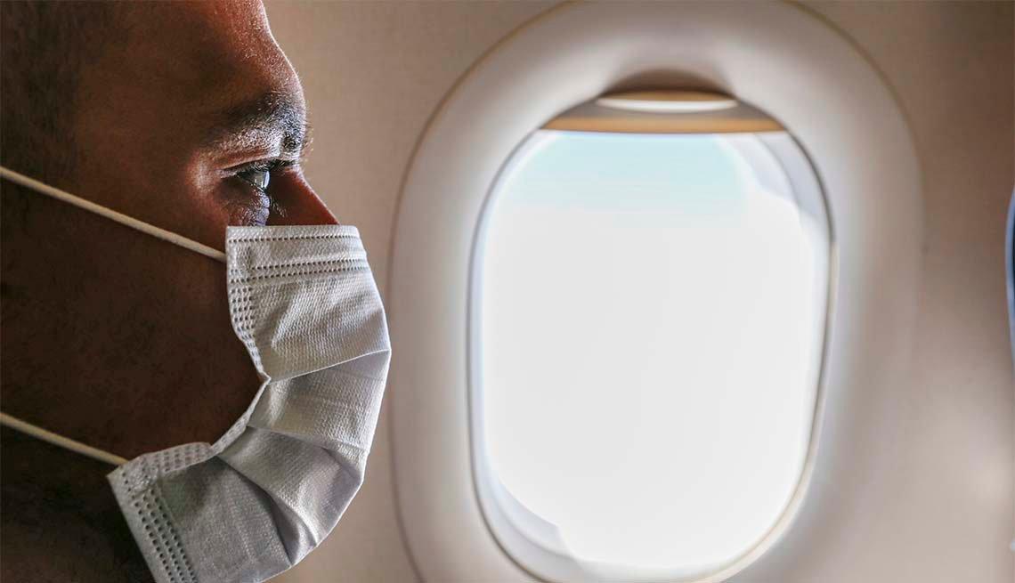 Un hombre lleva puesta una mascarilla dentro de un avión