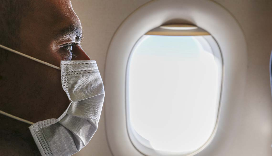 man wearing face mask on an airplane