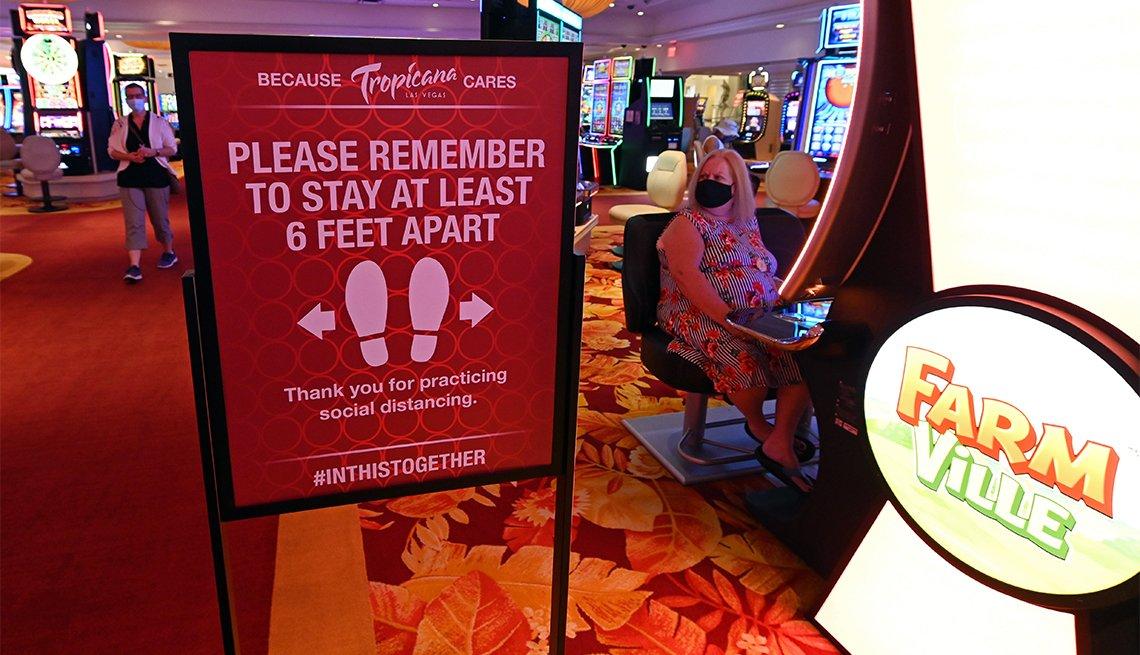 Mujer juega una máquina tragamonedas junto a un cartel de distanciamiento social