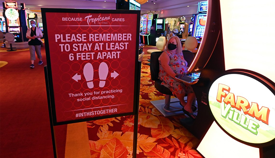 woman plays a slot machine next to a social distancing sign at the Tropicana Las Vegas