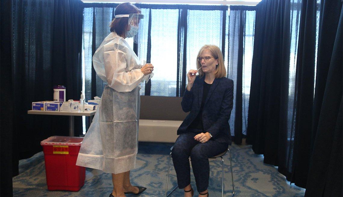 Mujer hace la prueba de COVID-19 a una viajera en el aeropuerto de Tampa