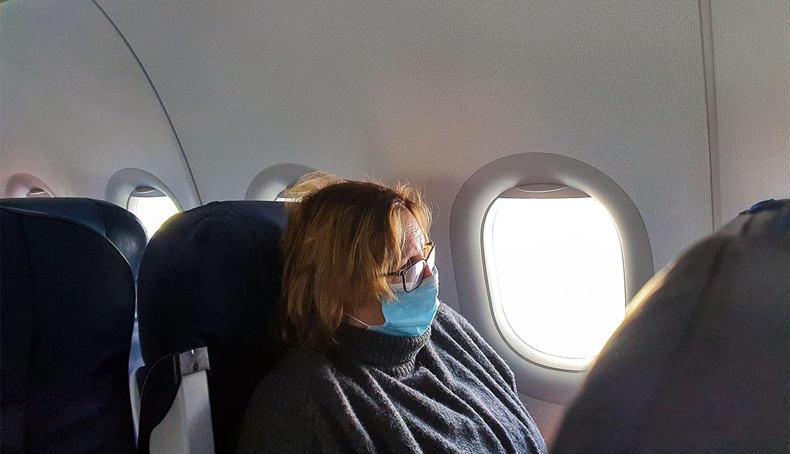Mujer viaja en avión y lleva puesta una máscara médica