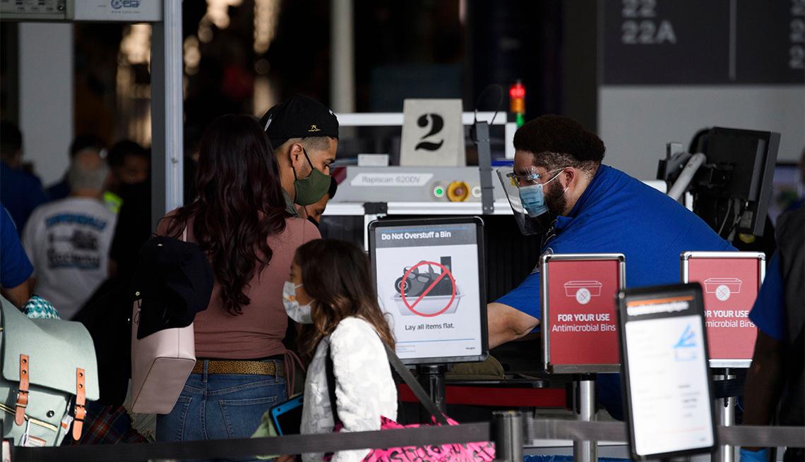 Personas pasan por un puesto de control en un aeropuerto