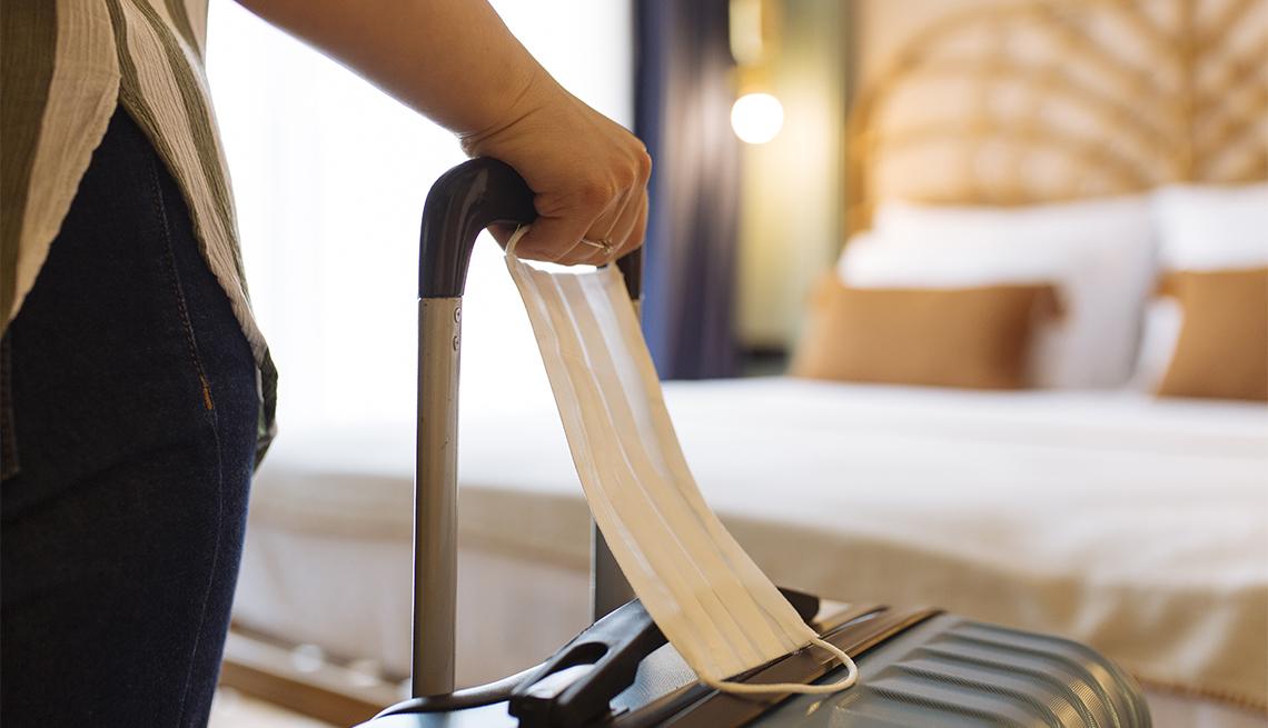 Mujer con mascarilla quirúrgica llega con una maleta a una habitación del hotel