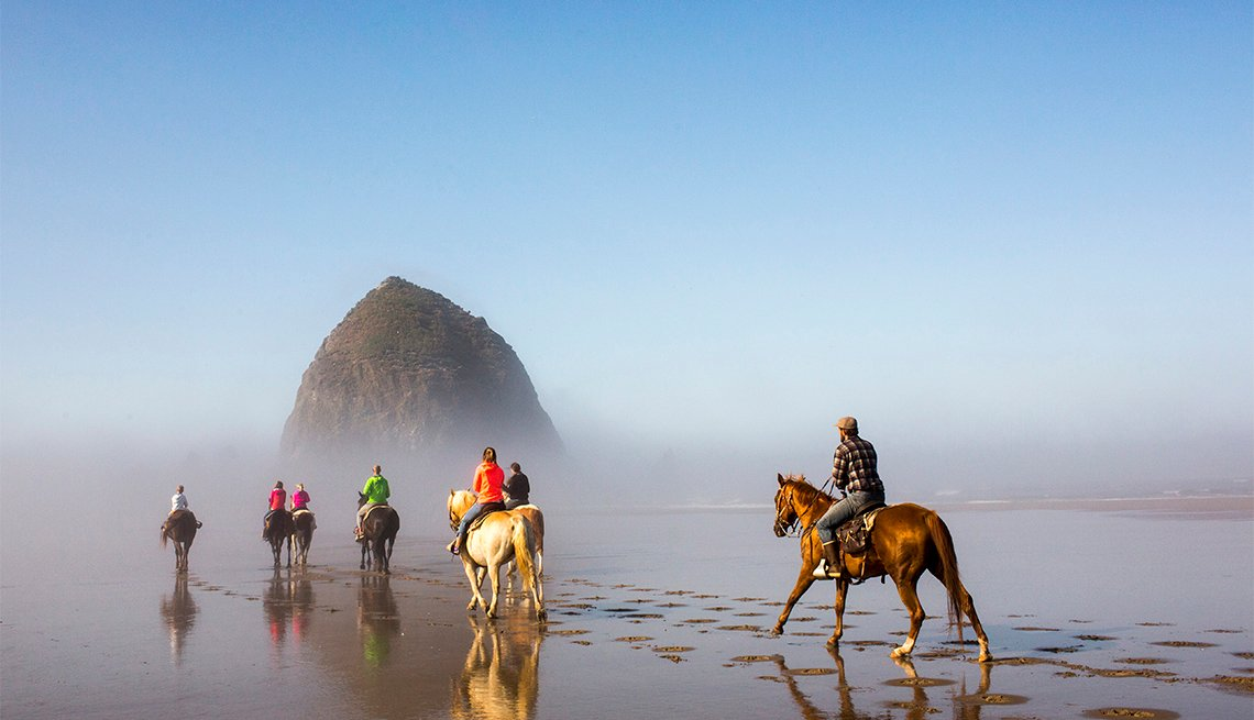 People horseback riding on beach