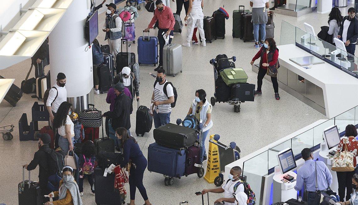 Viajeros con mascarillas quirúrgicas hacen fila para registrarse en sus respectivos vuelos