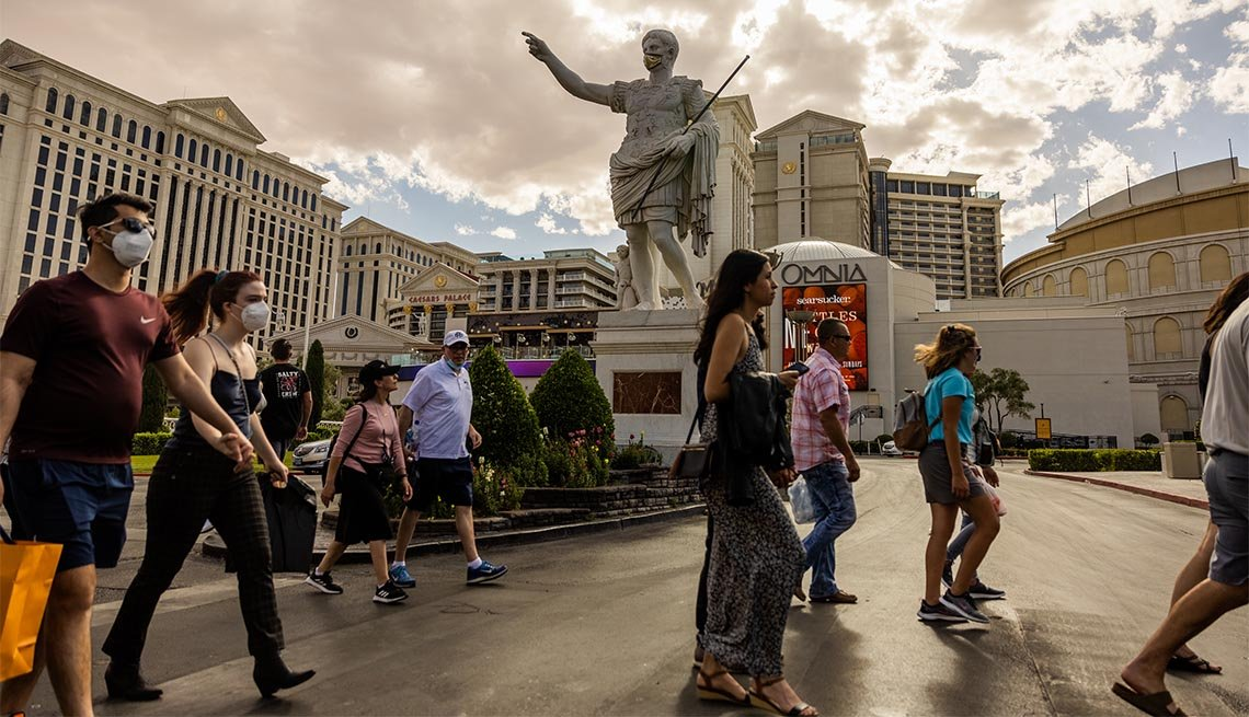 Pedestrians pass in front of Caesars Palace