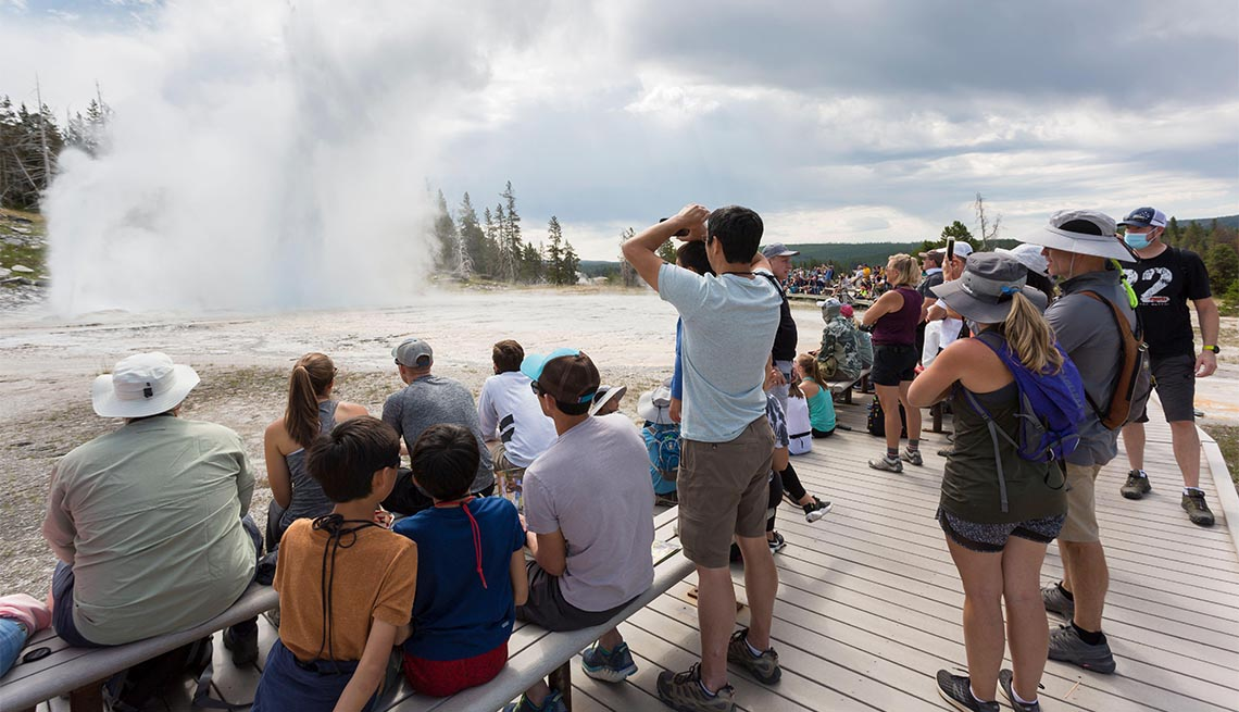 Visitors crowd the boardwalk as Grand Geyser erupts in Yellowstone National Park