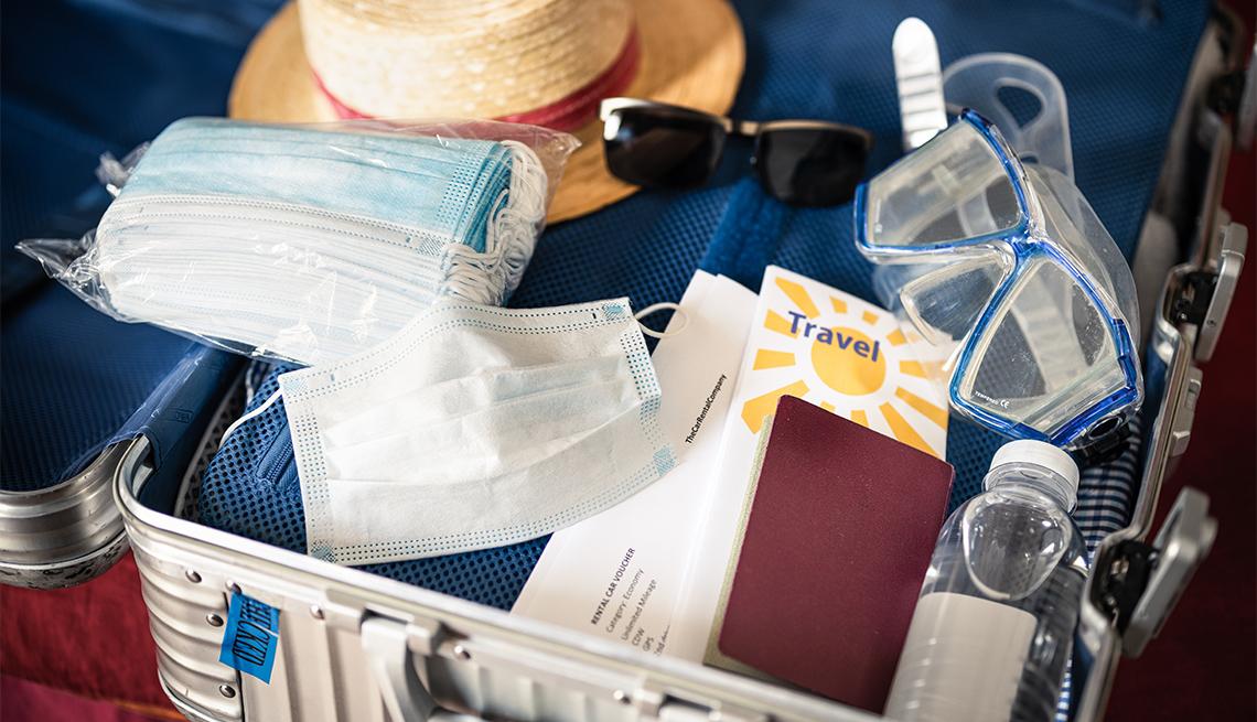 Maleta de viaje llena de desinfectante de manos, mascarillas y ropa