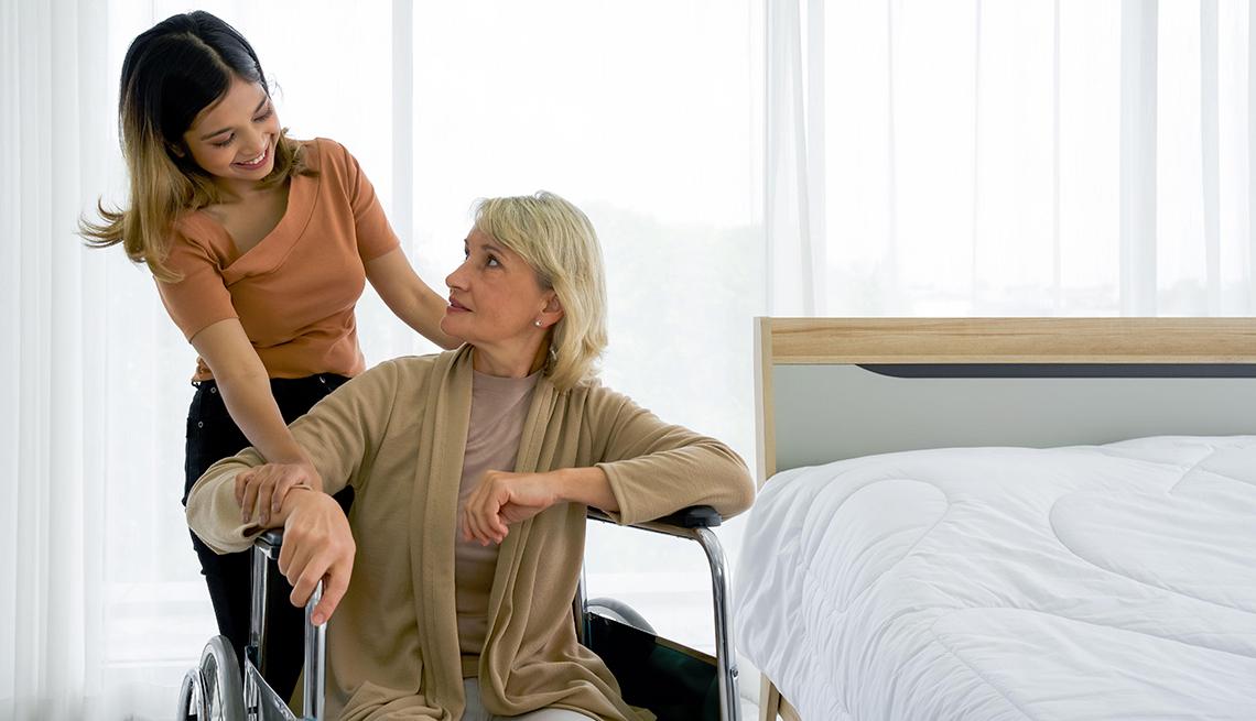Una niña de pie junto a su abuela en silla de ruedas en una habitación de hotel