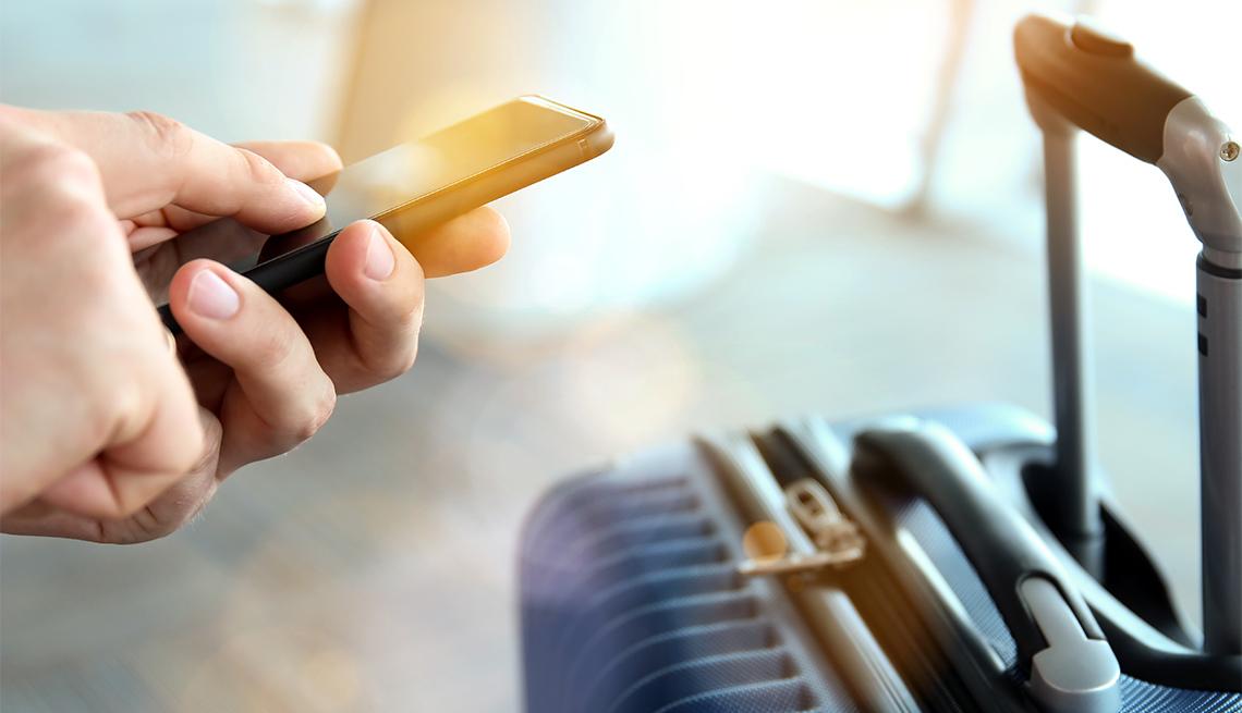 Persona espera en el aeropuerto con el teléfono en la mano