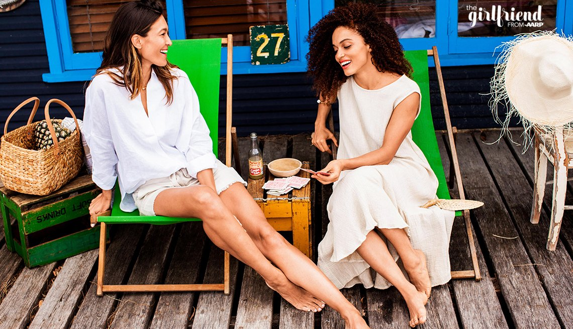 two women sitting on beach lounge chairs playing cards