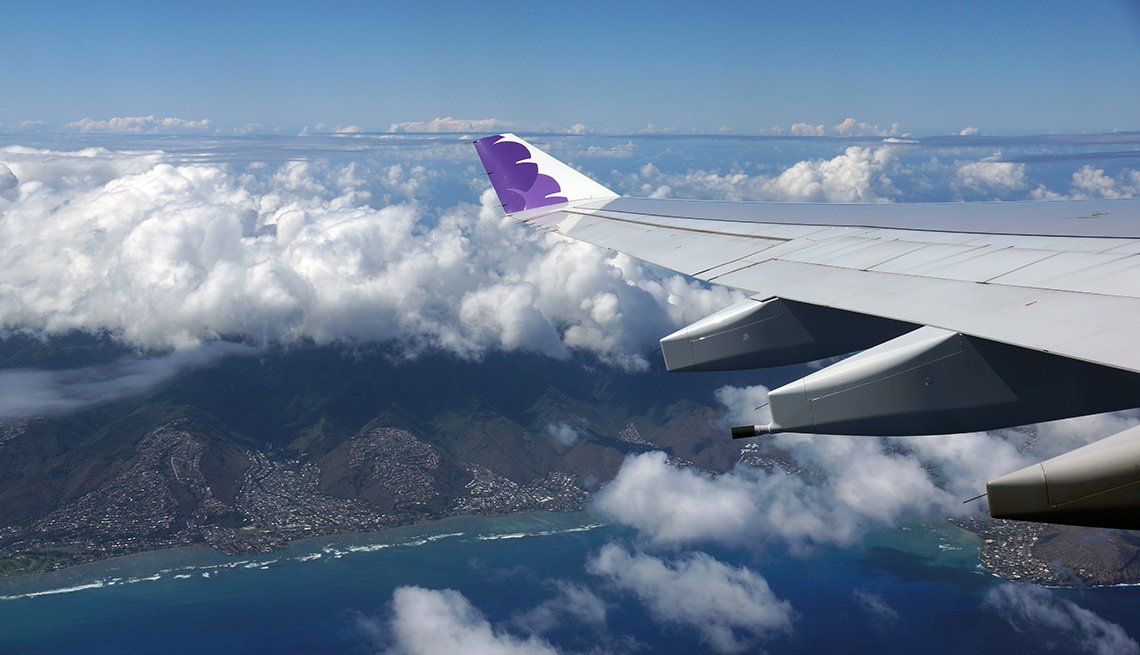 Wing of Hawaiian Airlines plane flying in the air above Honolulu, Hawaii