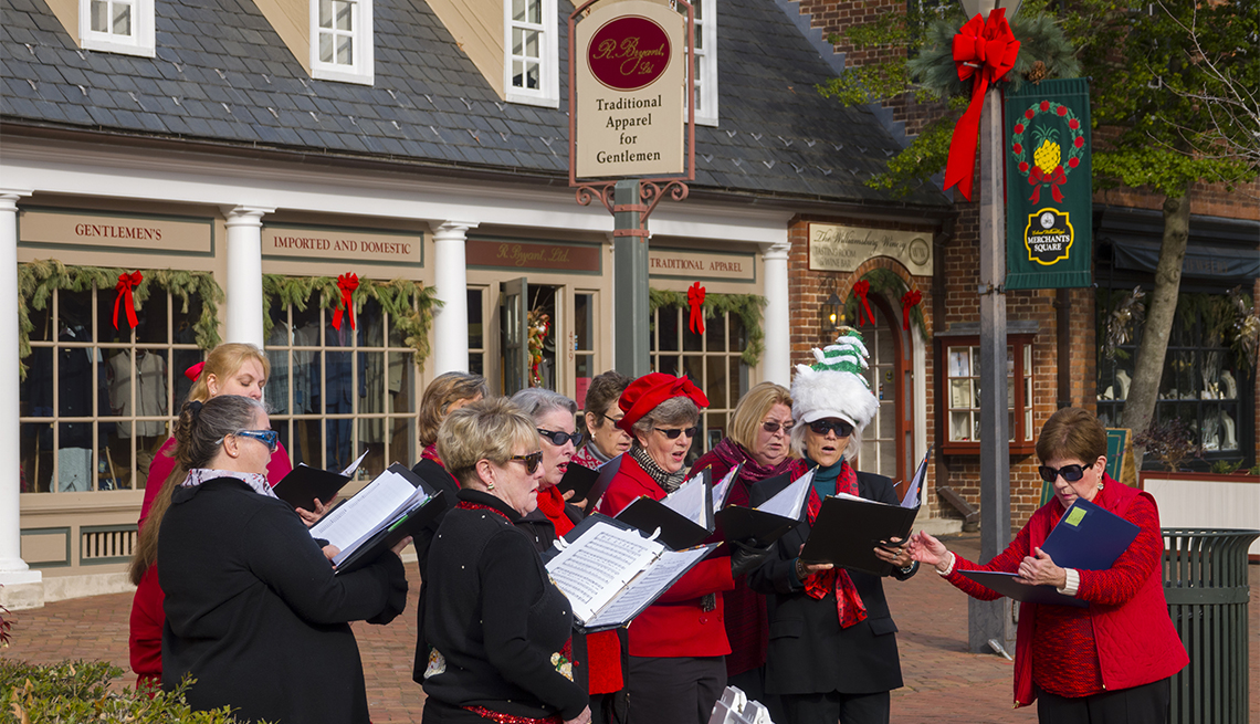 item 3 of Gallery image - a group of female carolers singing outside a store during holiday season