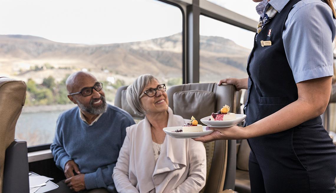 item 6 of Gallery image - Camarera ofrece postre a un hombre y una mujer en el tren Rocky Mountaineer