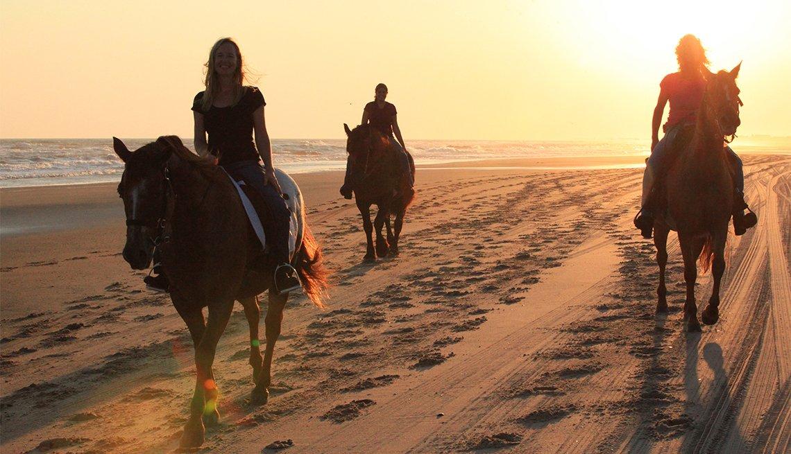 Tres personas montan a caballo en la playa
