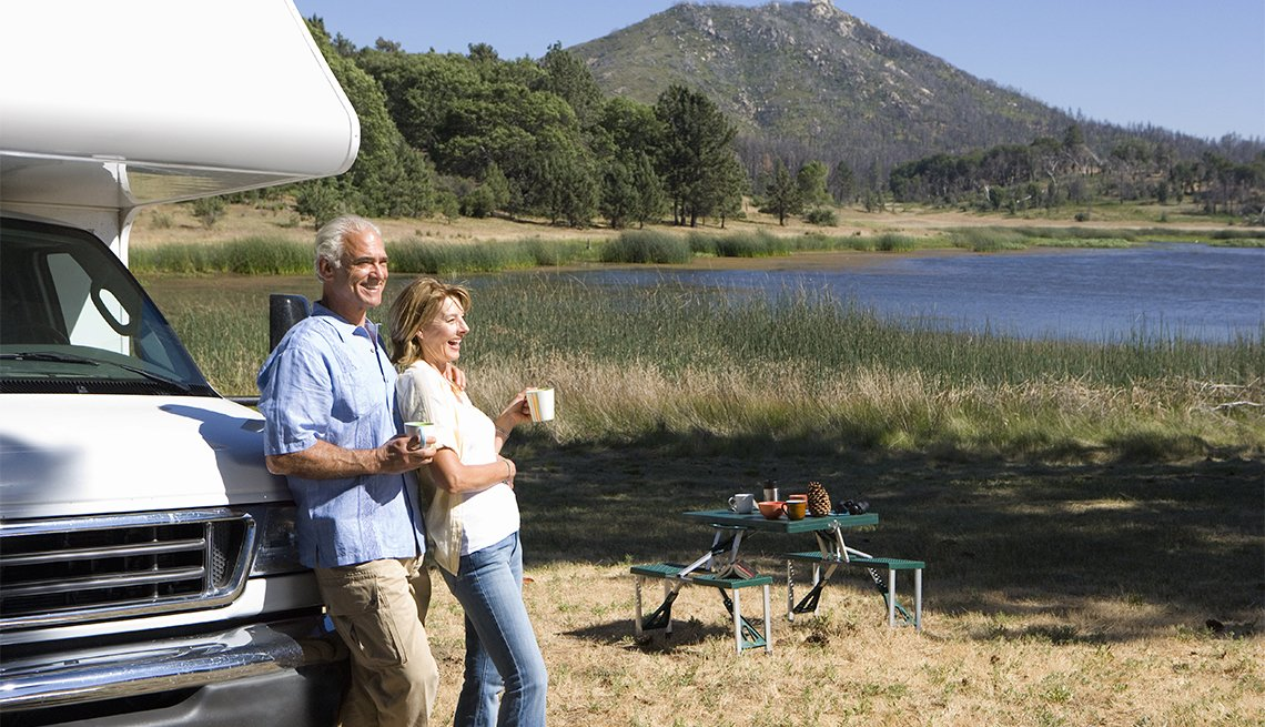 couple relaxing in countryside by lake on motor home vacation