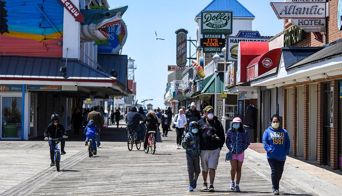 Gente camina por el paseo marítimo de Ocean City, MD