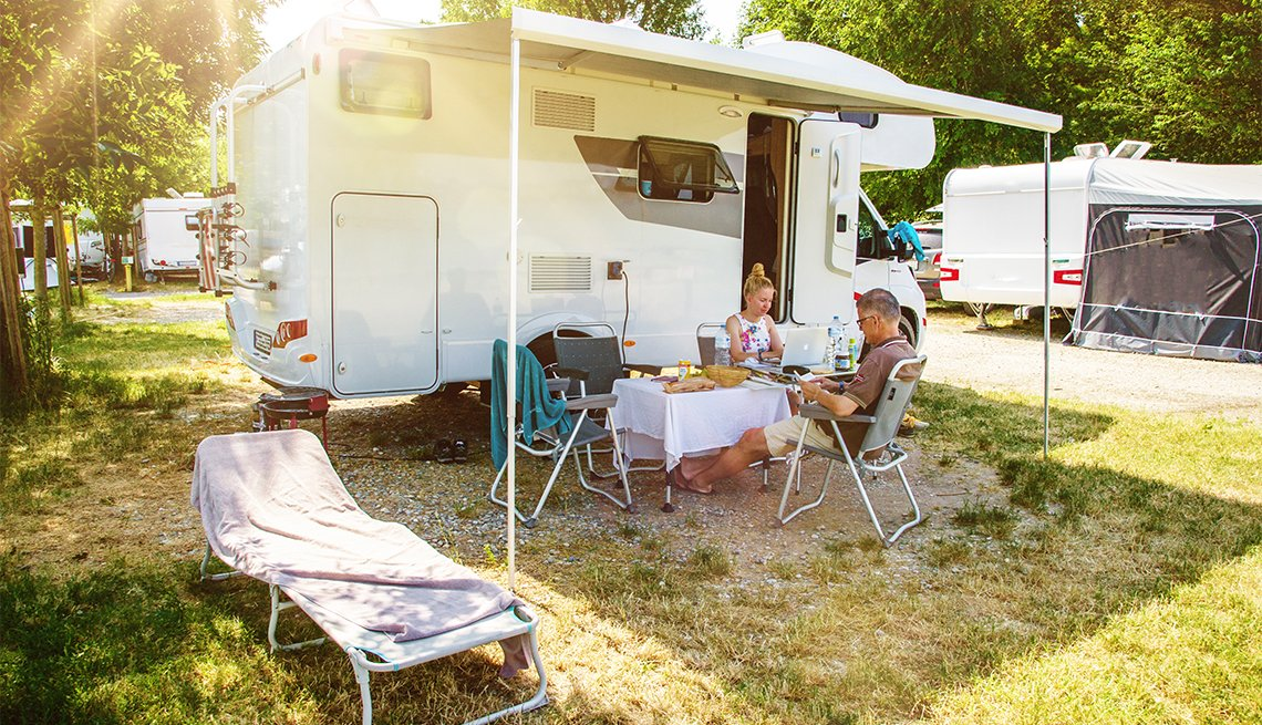 Reading couple, sitting at a camping table in front of a motorhome on a sunny day in summer
