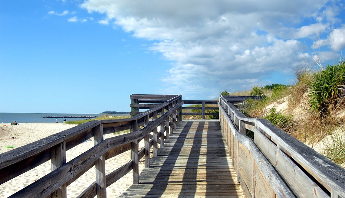 Wooden dock, with late afternoon shadows, partition off sand dunes from Cape Charles Beach on the Island of Assateague, Virginia.