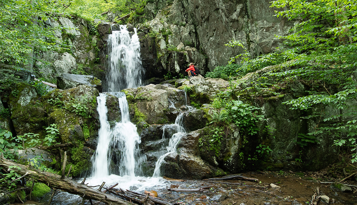 Man exploring idyllic forest waterfall in Shenandoah National Park, Virginia