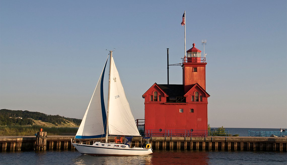Sailboat entering harbor channel Holland State Park Michigan passing Big Red the entry lighthouse