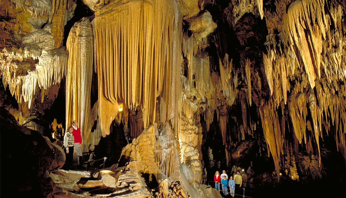 Visitors admire the intricate patterns of enormous and stalactites extending from the roof and floor, Luray Caverns