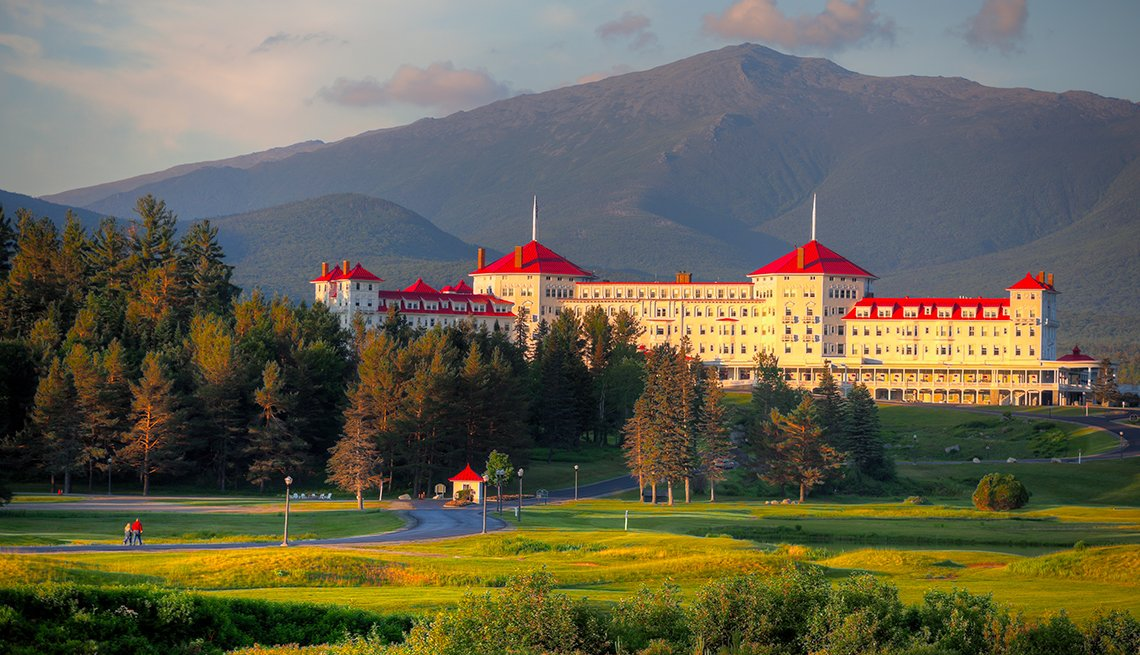 beautiful old hotel with white walls and red roof in a picturesque mountain setting