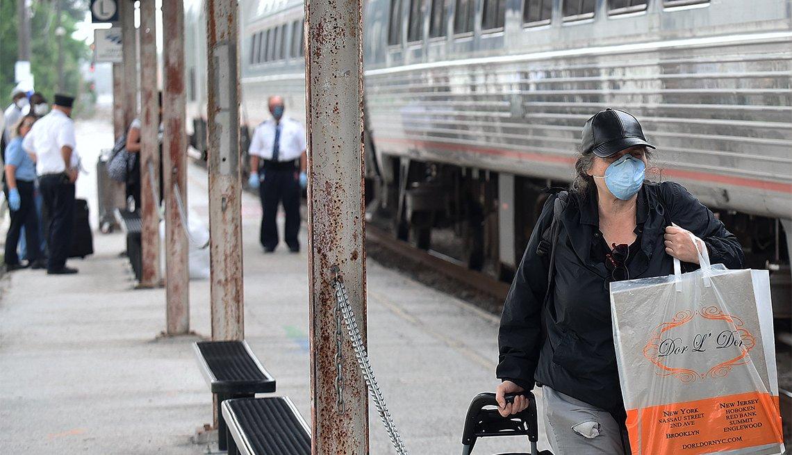 Mujer lleva puesta una máscara mientras pasa junto a un tren Amtrak