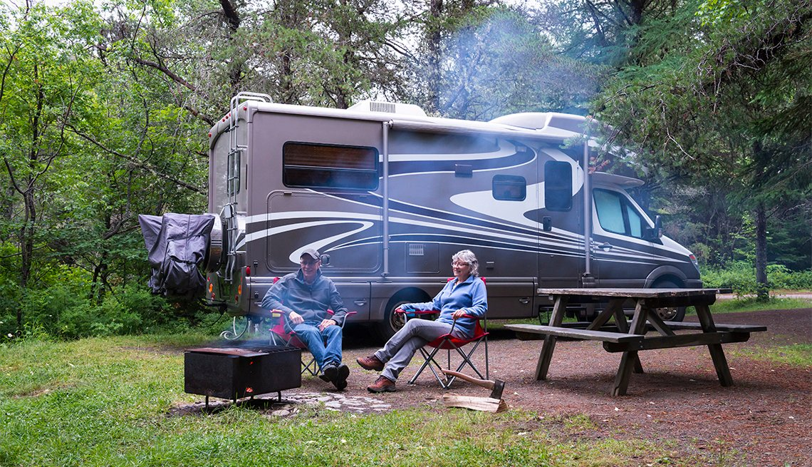 Couple relaxing near campfire with an RV in the background