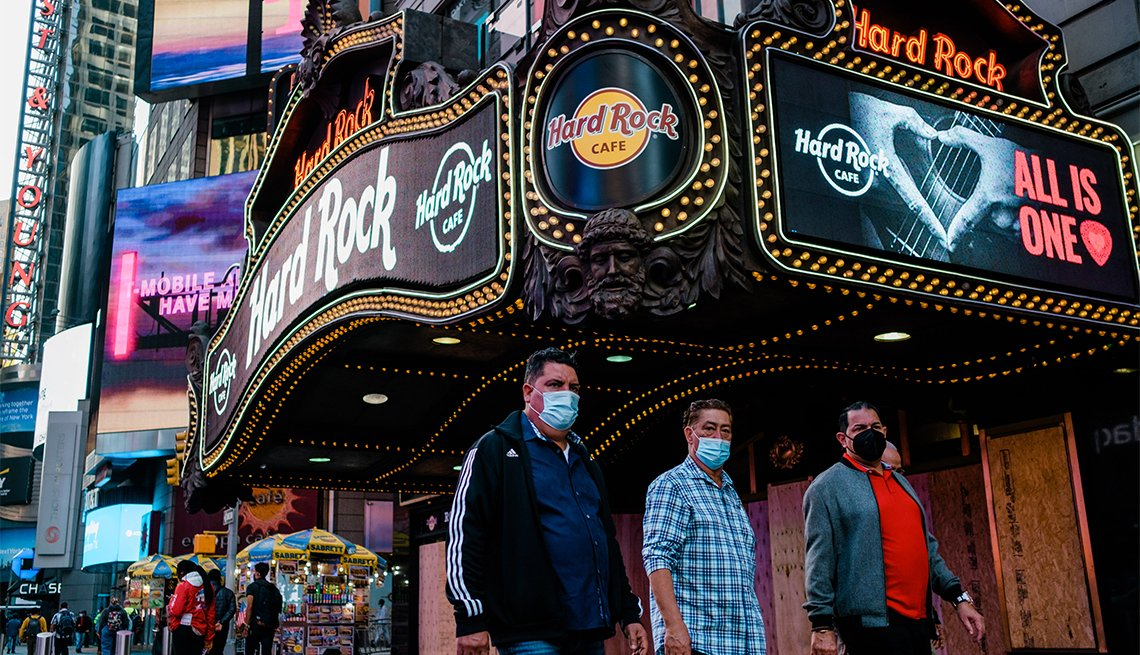 Pedestrians wearing protective mask pass in front of the Hard Rock Cafe in the Times Square neighborhood of New York