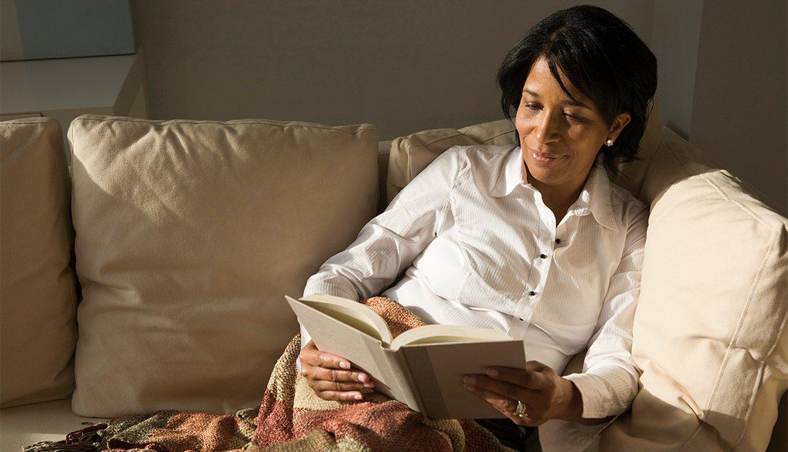 Mujer sentada en un sofá lee un libro