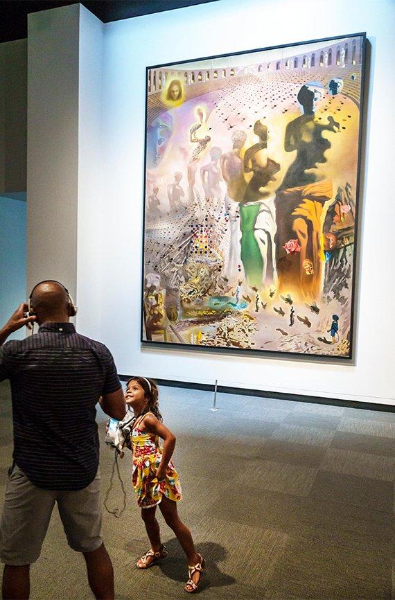 Un hombre con una niña observan una pintura en el Museo Dalí