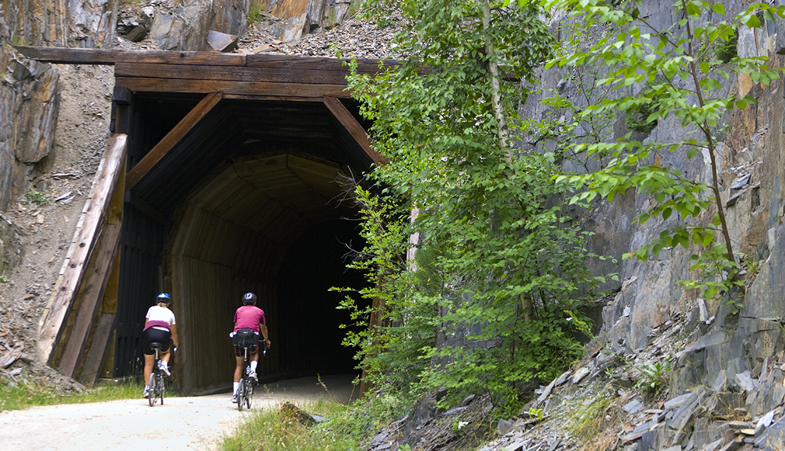 item 1 of Gallery image - two people riding bikes on a rails to trails bike trail in front of a tunnel