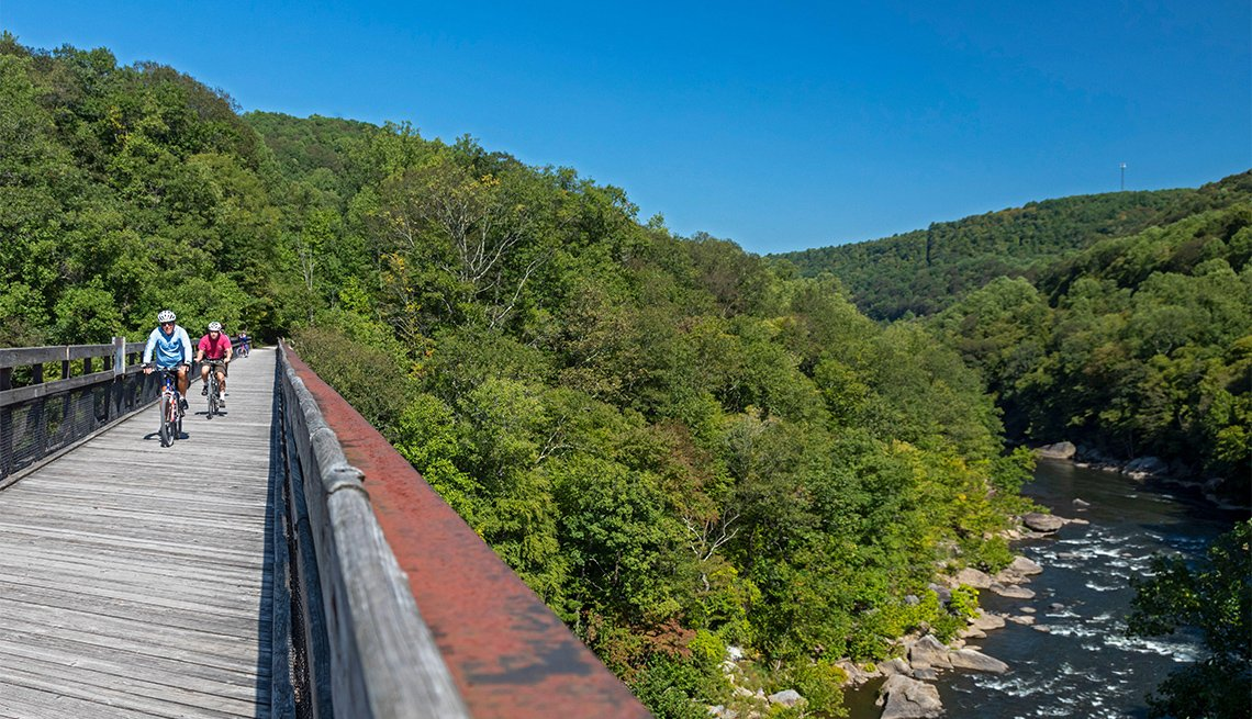 Bicycle riders cross a bridge over the Youghiogheny River on the Great Allegheny Passage trail