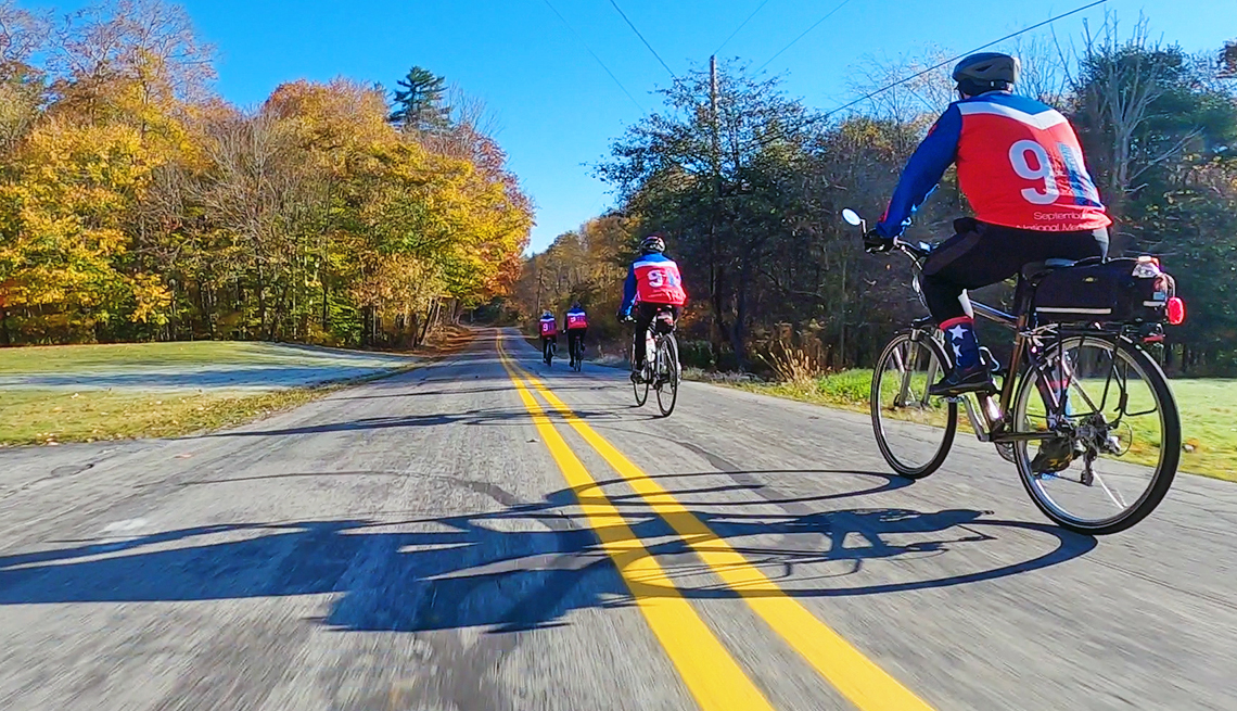 four people on bicycles wearing jerseys commemorating 9 11 riding on a country road