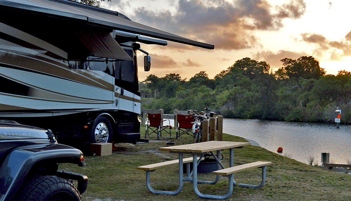 An RV near a lake with outdoor seating at Phipps Parks Florida
