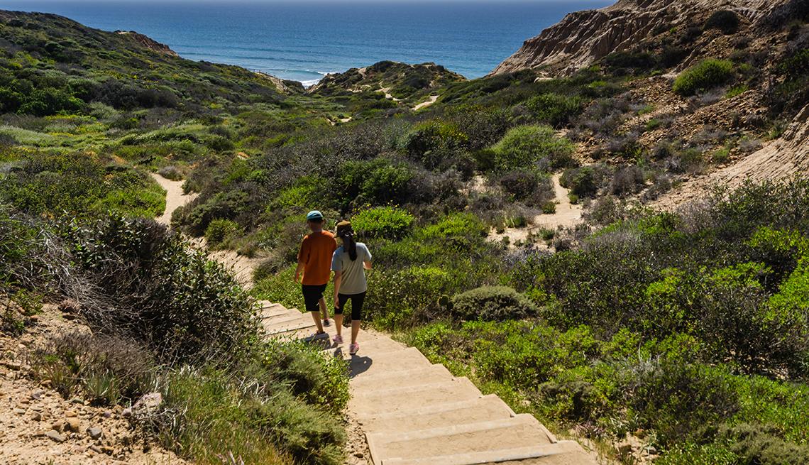 Un hombre y una mujer caminando por una colina empinada