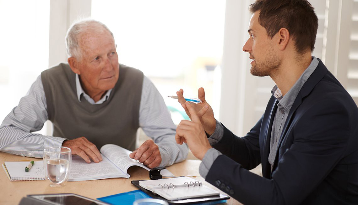 Two men sitting at a table with paper work discussing fraud prevention