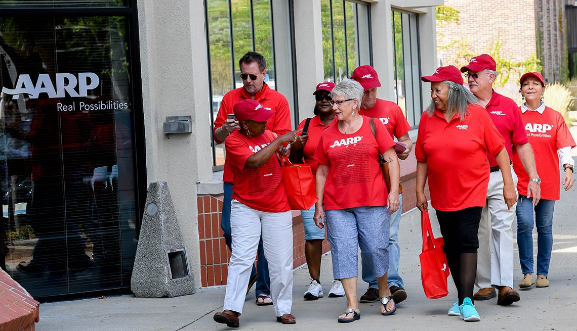 An group from an a a r p chapter walking down the street wearing red a a r p t shirts