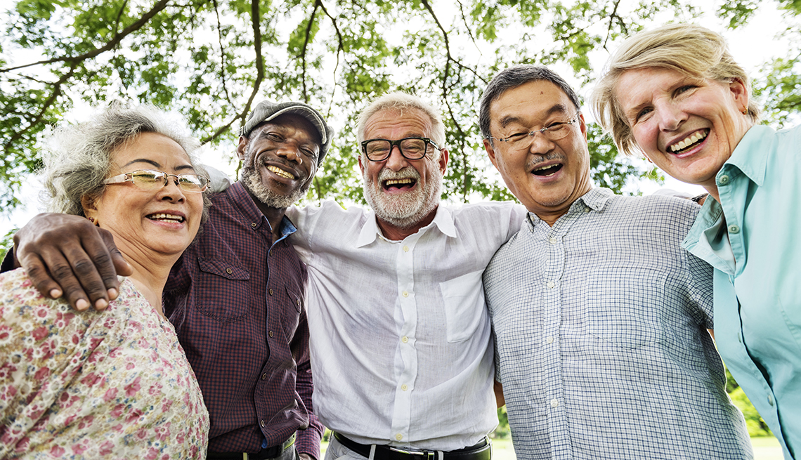 A diverse group of two women and three men smiling