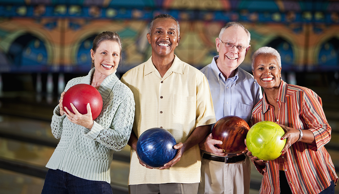 Two couples holding bowling balls at a bowling alley