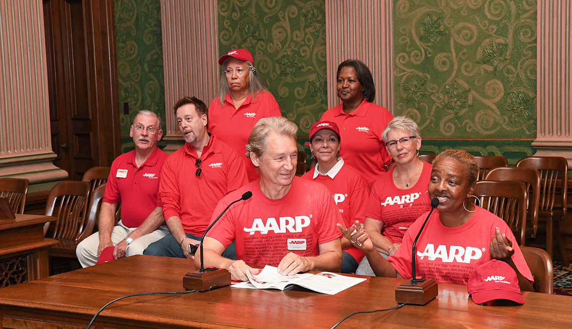 A group of volunteers speaking at the state capitol