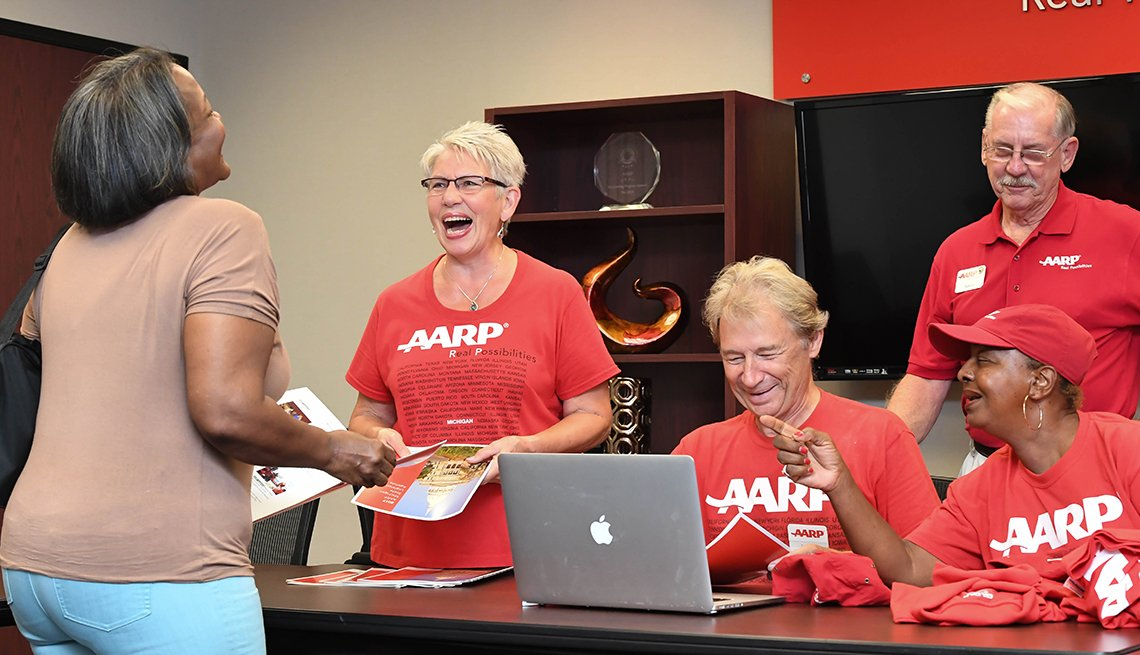 A group of a a r p volunteers handing out flyers and t shirts and laughing