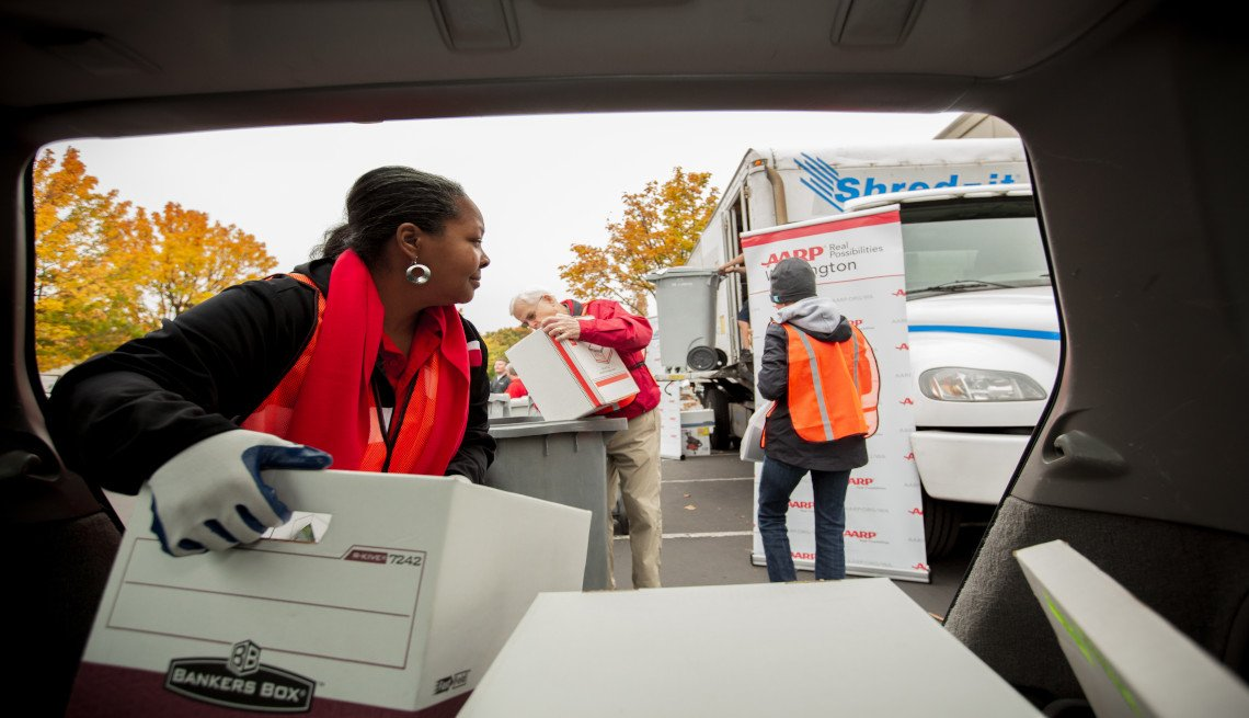 A female volunteer moving out paper boxes from a van at a shred event