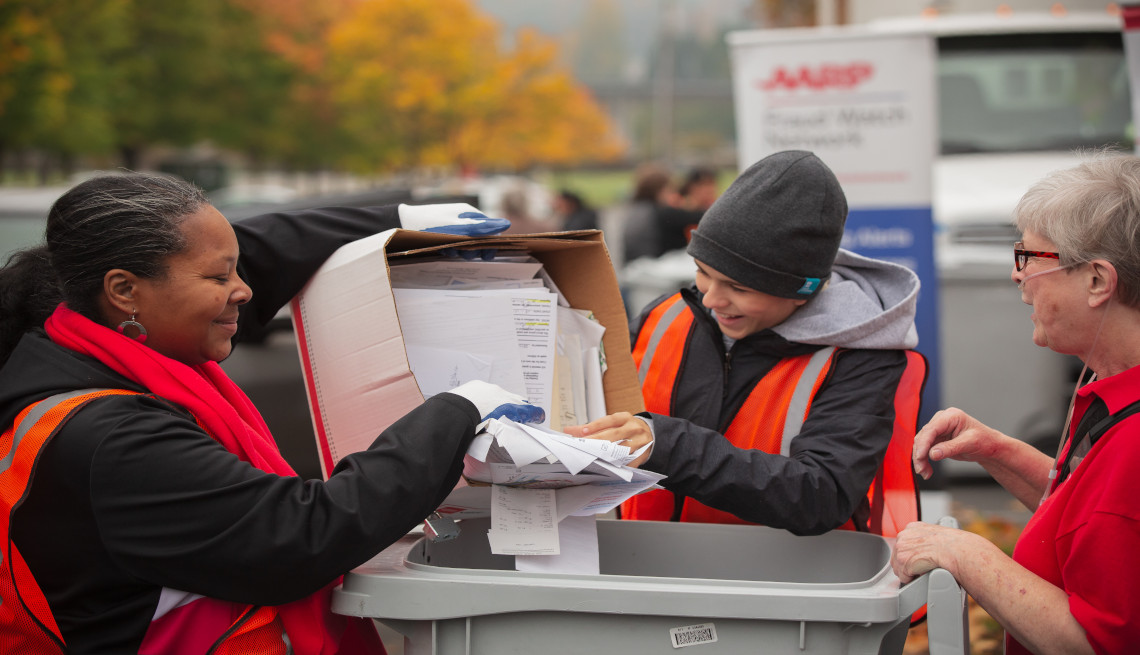 Volunteers disposing documents into trash bins on the occasion of paper shredding event