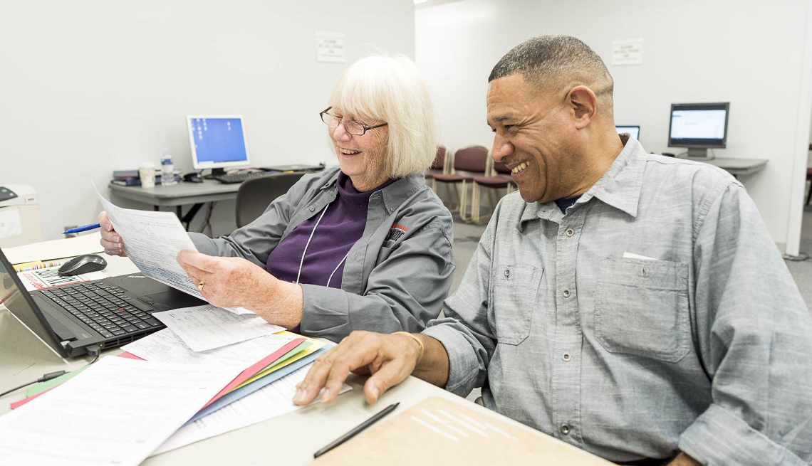 a female tax aide volunteer reviewing tax paper work with a male client