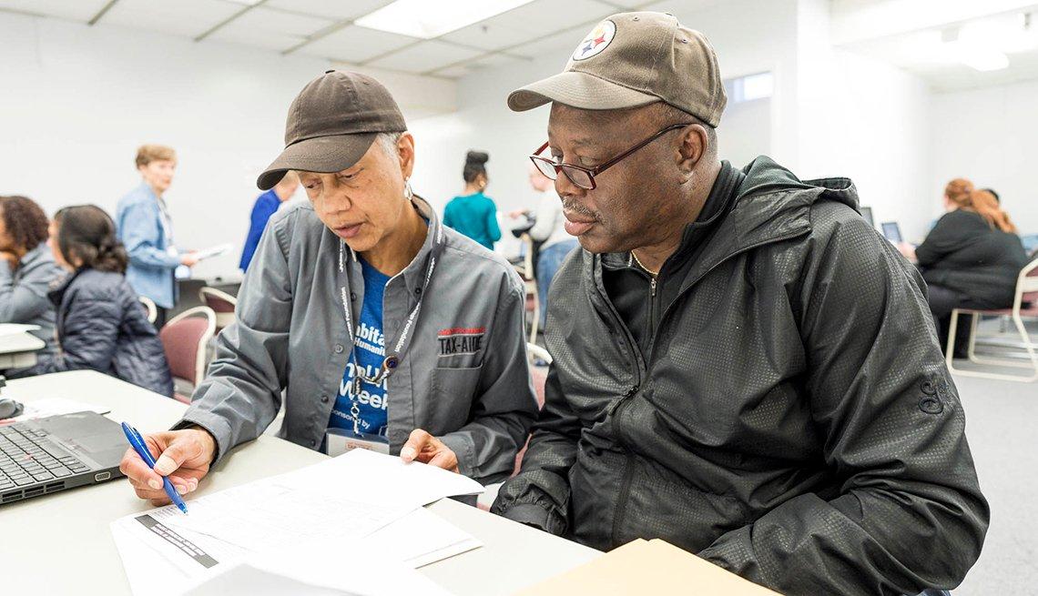 An A A R P tax aide volunteer helps a man look through his tax filing paperwork
