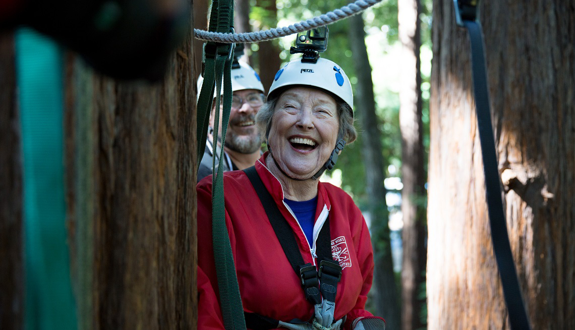 A woman on a zip line in the woods laughing