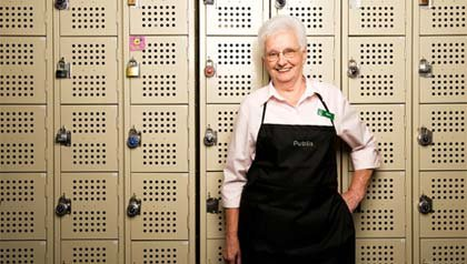 Empleos para personas mayores - Mujer con delantal recostada sobre unos casilleros.